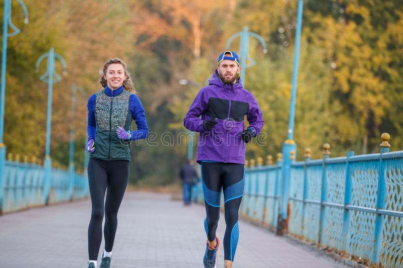 Runners fitness couple jogging in the city park stock image