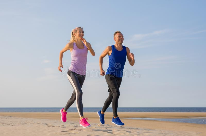 Runners fitness couple running training on the beach stock images