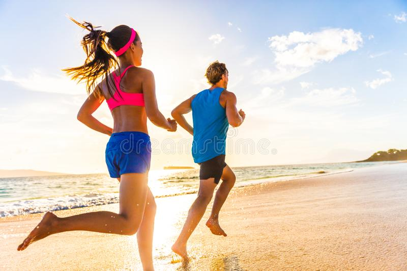 Runners fitness couple running training on beach. Morning cardio workout people doing exercise. ctive sports lifestyle. Runners fitness couple running training royalty free stock photography