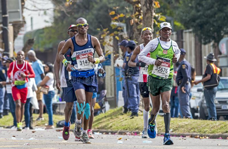 Runners Participating in the Comrades Marathon in South Africa. PINETOWN, DURBAN, SOUTH AFRICA - JUNE 10, 2018: Midday many spectators and unknownn runners royalty free stock images