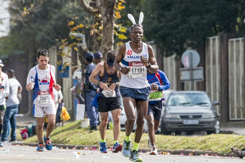 Runners Participating in the Comrades Marathon in South Africa. PINETOWN, DURBAN, SOUTH AFRICA - JUNE 10, 2018: Midday many spectators and unknownn runners stock photography