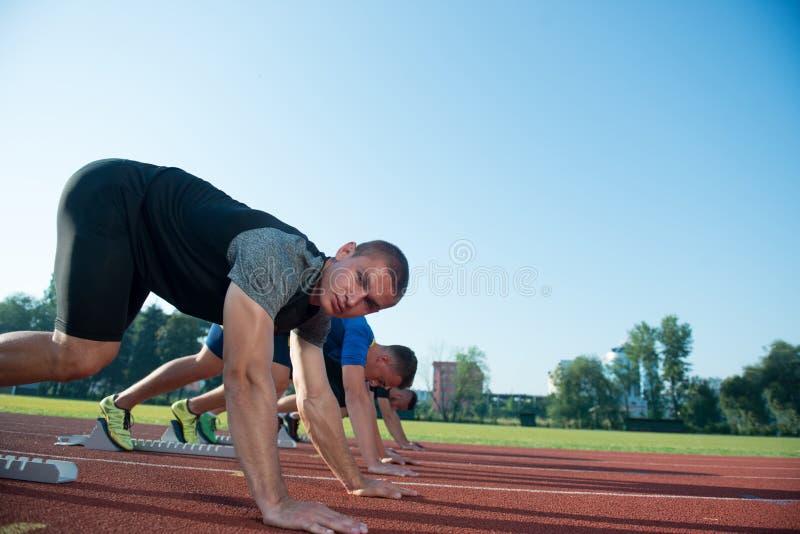Runners preparing for race at starting blocks royalty free stock image