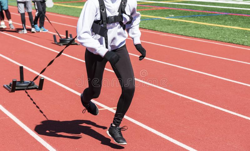 Runners pulling weighted sleds on a track royalty free stock images