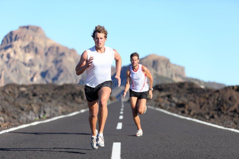 Runners running on road stock image