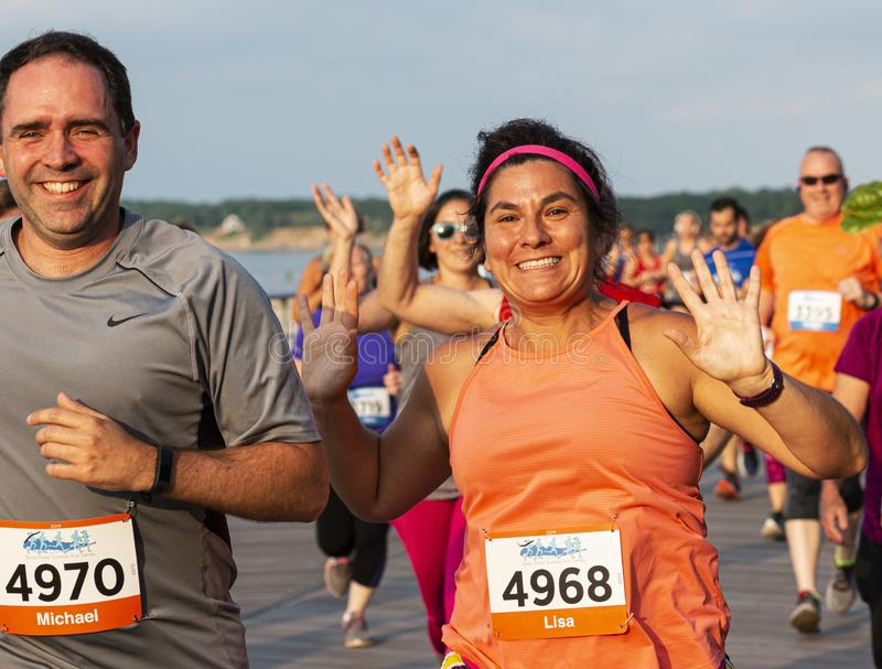 Runners smiling and waving while racing on a boardwalk in the New York State Summer Series stock photo