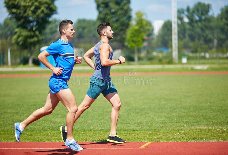 Runners on track stock photos