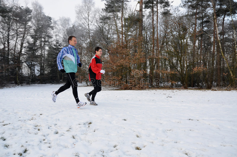 Runners in wintertime. Runners in the snow in winter stock image