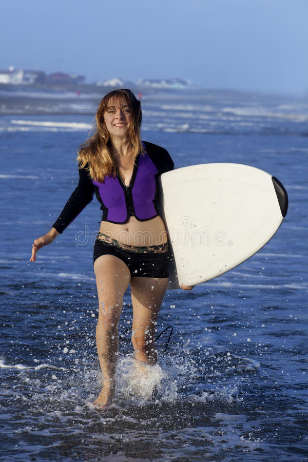 Runnibg de femme avec la planche de surf photos stock