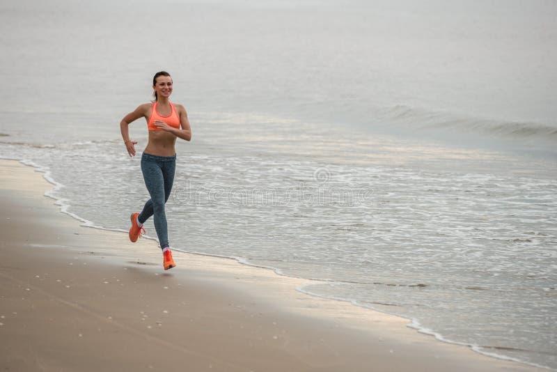 Runnig da mulher do esporte na praia imagens de stock