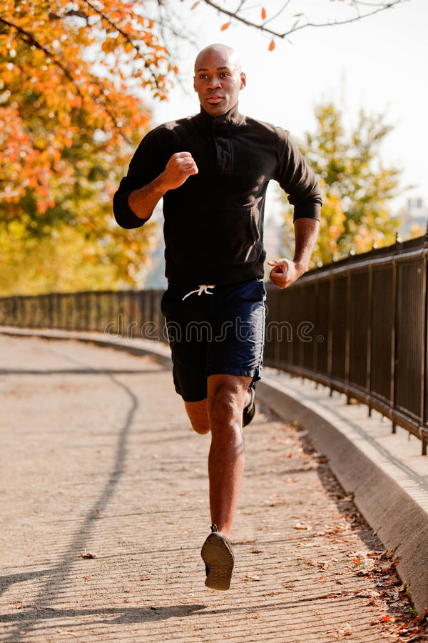 Running. An African American jogging in a park in the morning royalty free stock photography