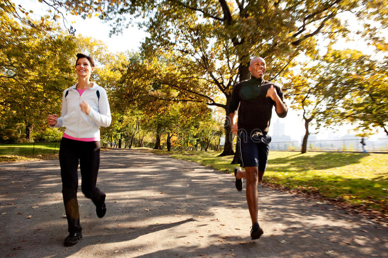 Running. Two runners in a park with slight motion blur stock photography