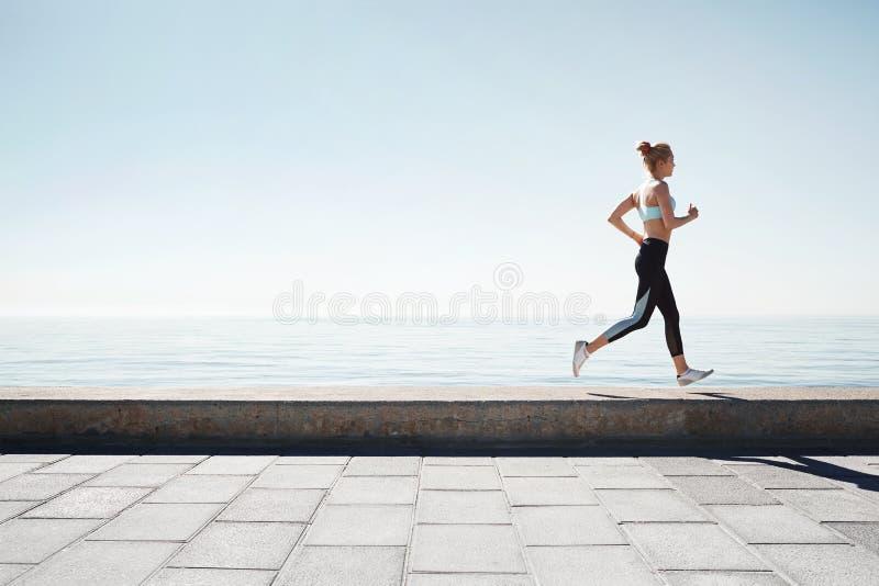 Running asian woman. Female runner training outdoors seaside stock images