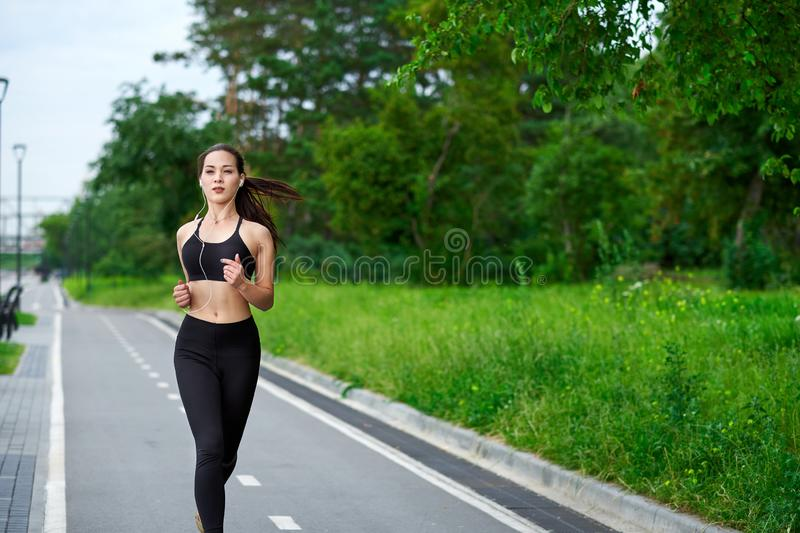 Running asian woman on running track. Morning jogging. The athlete training stock photography