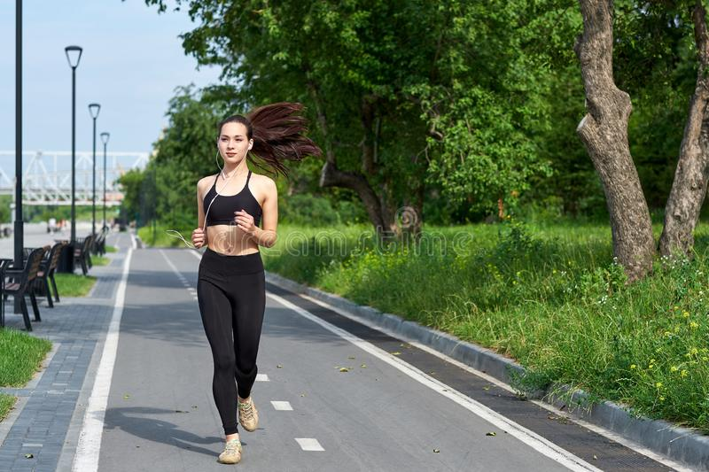 Running asian woman on running track. Morning jogging. The athlete training royalty free stock image