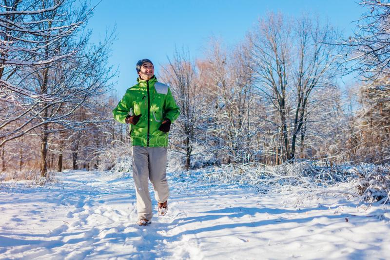 Running athlete man sprinting in winter forest. Training outside in cold snowy weather. Active healthy way of life royalty free stock photography