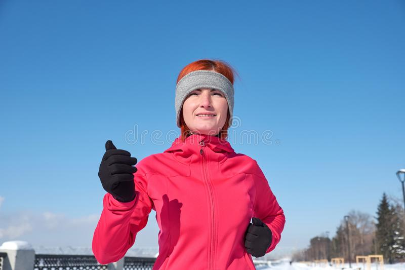 Running athlete woman sprinting during winter training outside in cold snow weather. Close up showing speed and movement stock images