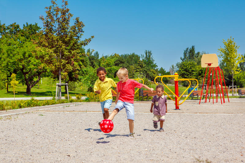 Running with a ball. Excited kids running with a ball on the playground royalty free stock photos