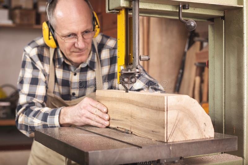 A running bandsaw with a carpenter working it. A carpenter in his 50th is working on a bandsaw. He is cutting a piece of wood while wearing ear protectors, a stock photography
