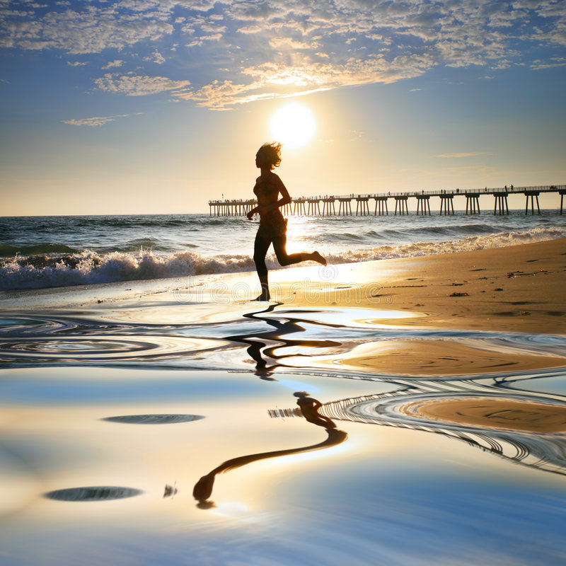 Running on beach. Woman at the beach running by the ocean at sunset royalty free stock photography