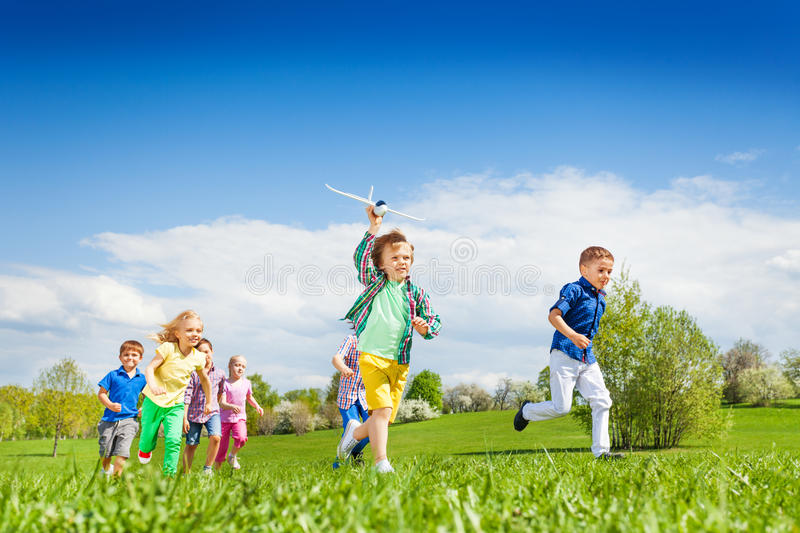 Running boy with airplane toy and other children royalty free stock images
