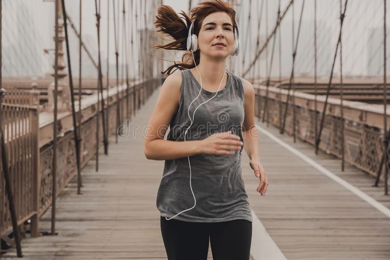 Running on Brooklyn bridge. Woman practicing jogging on the Brooklyn bridge stock photo