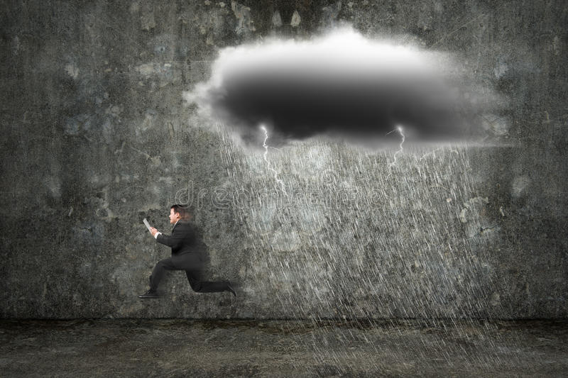Running businessman holding tablet with dark clouds raining and. Lightning on concrete wall background stock photo