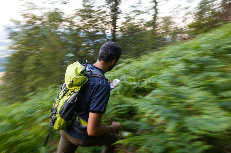 Running for a cache. Hiker searching cache using global positioning device. Panning. Motion blur stock images