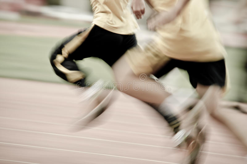 Running child on sport track. Blurred motion abstract background royalty free stock image