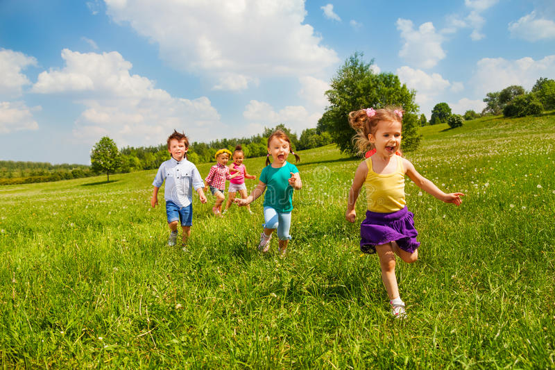 Running children in green field during summer royalty free stock photos