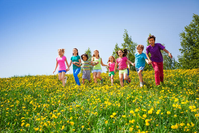 Running children holding hands in meadow royalty free stock image