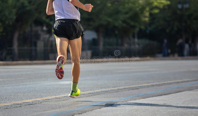 Running in the city roads. Young man runner, back view, blur background, copy space stock photo