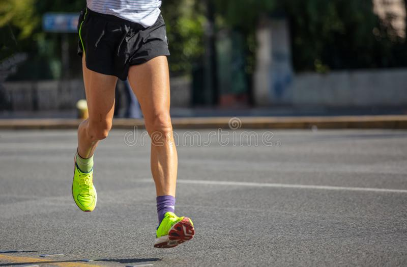 Running in the city roads. Young man runner, front view, blur background, copy space stock photography