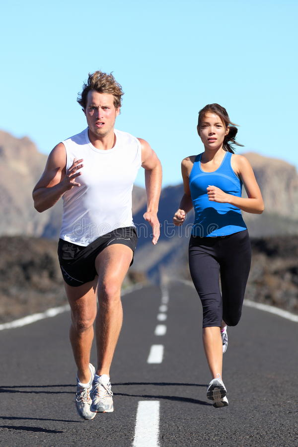 Running couple. Runners outdoor jogging workout on road beautiful landscape. Fit athletes training, Caucasian man, Asian woman