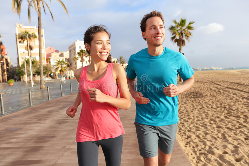 Running couple jogging Barcelona Beach Barceloneta stock image