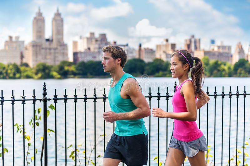 Running couple runners training, Central Park, NYC. Running couple runners jogging in Central Park, NYC livng healthy fitness lifestyle. People running summer stock image