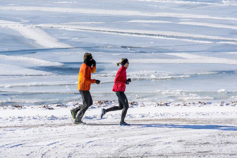 Running couple in a winter day royalty free stock photo