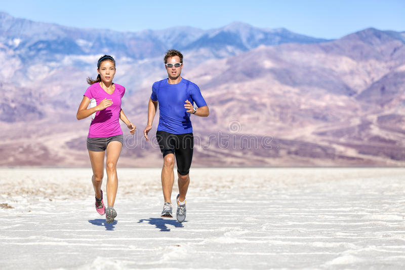Running Determined Couple Jogging Against Mountain. Running Fitness people. Full length of determined couple jogging against mountains. Young partners are in royalty free stock photos