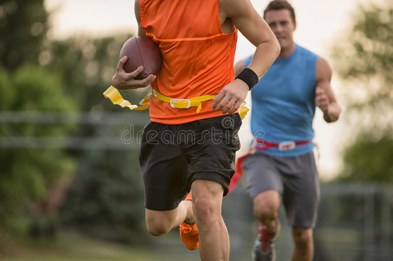 Running Down The Field. Guys playing flag football on a warm autumn day stock photo