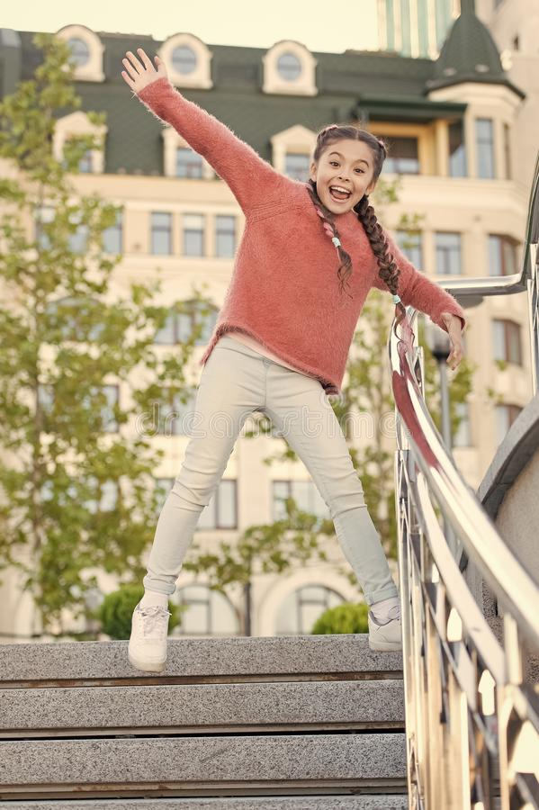 Running down the stairs. Happy energetic kid jumping on steps in casual wear. Energetic little girl with long hair stock images