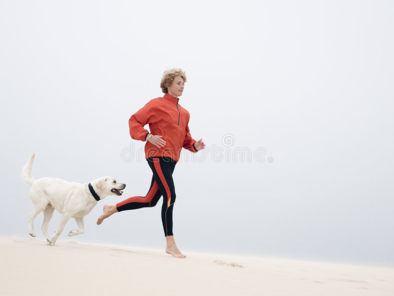 Running on the dune. Woman running with labrador retreiver on dune