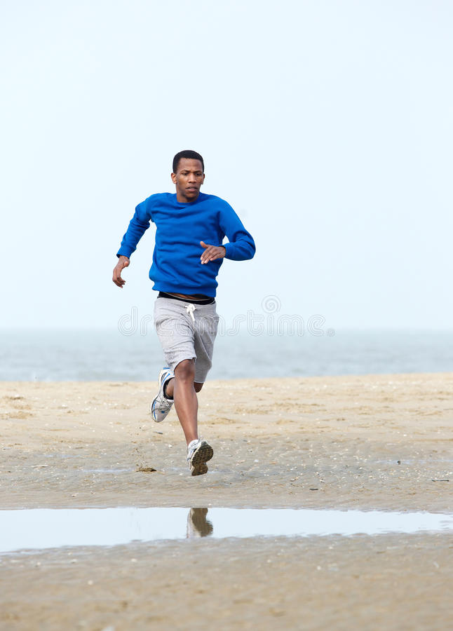 Running exercise. Active young man jogging at the beach. Running exercise royalty free stock photography