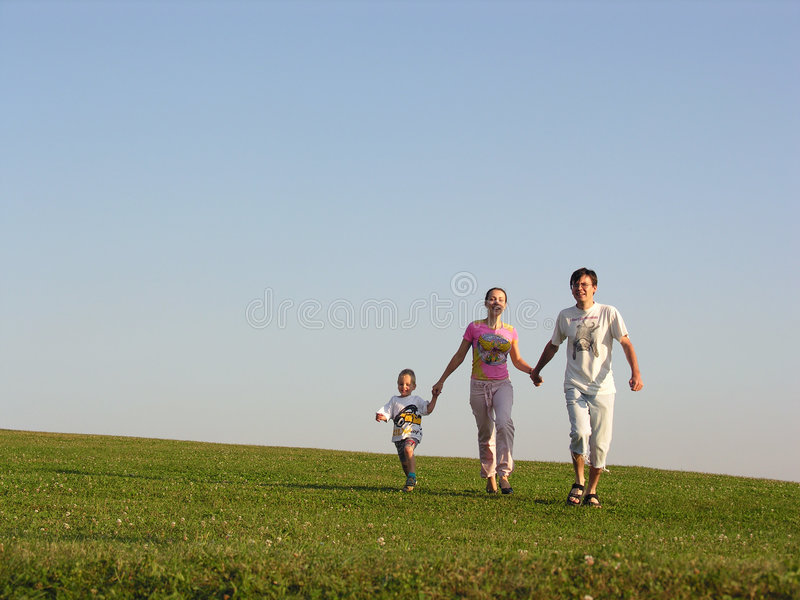 Running family. Blue sky green grass sundown royalty free stock image