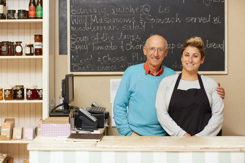 Running a family business. Two deli business owners behind the counter royalty free stock photography