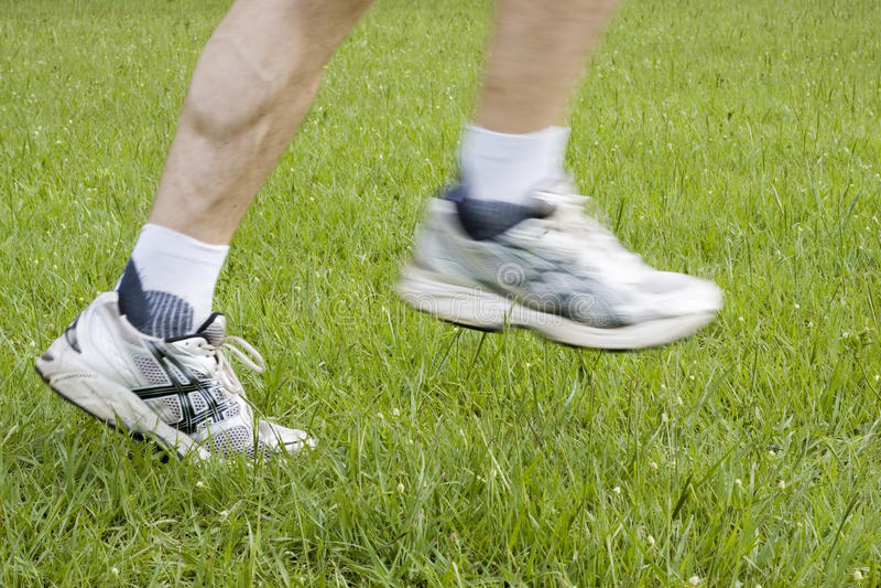 Running feet in green grass stock photo
