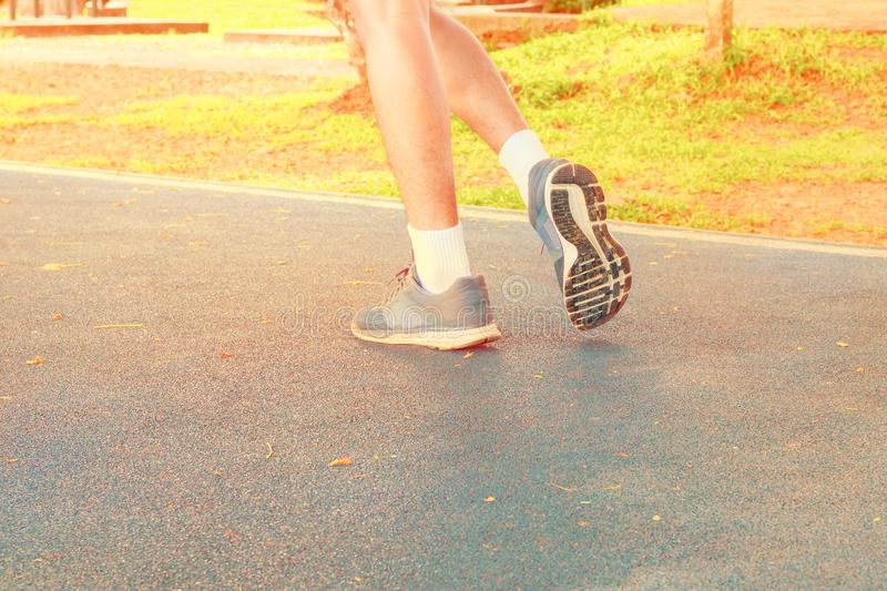 Running feet male in runner jogging exercise with old shoes for health lose weight concept on track rubber cover blue public park. Copy space add text. Vintage royalty free stock photo
