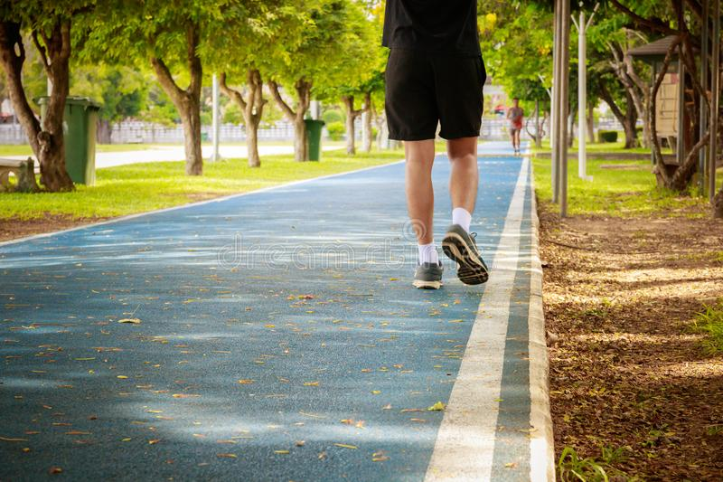 Running feet male in runner jogging exercise with old shoes for health lose weight concept on track rubber cover blue public park. Copy space add text stock photography