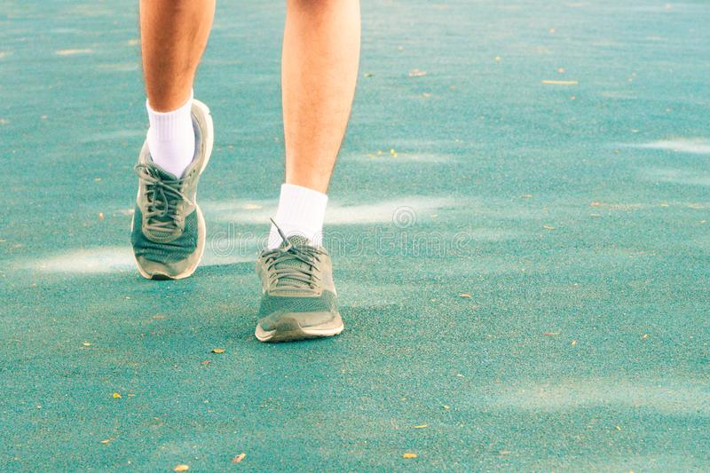 Running feet male in runner jogging exercise with old shoes for health lose weight concept on track rubber cover blue public park. Copy space add text. Vintage royalty free stock photography