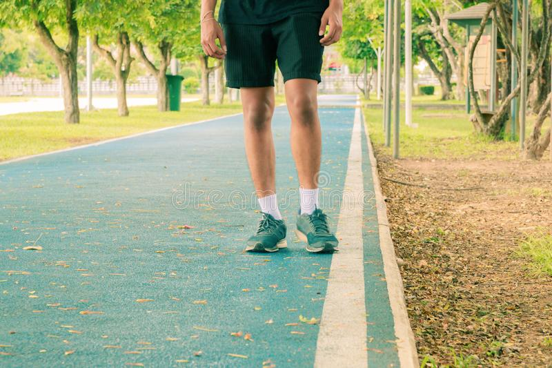 Running feet male in runner jogging exercise with old shoes for health lose weight concept on track rubber cover blue public park. Copy space add text. Vintage royalty free stock photos