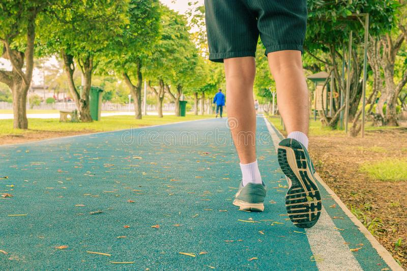 Running feet male in runner jogging exercise with old shoes for health lose weight concept on track rubber cover blue public park. Copy space add text. Vintage stock image