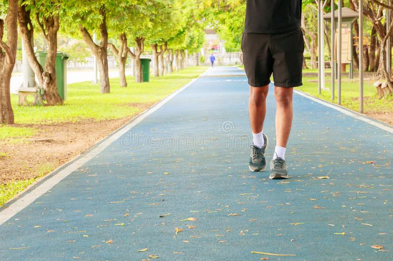 Running feet male in runner jogging exercise with old shoes for health lose weight concept on track rubber cover blue public park. Copy space add text royalty free stock photos